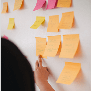 Close Up of Different Shades of Orange Post-It notes stuck to a wall