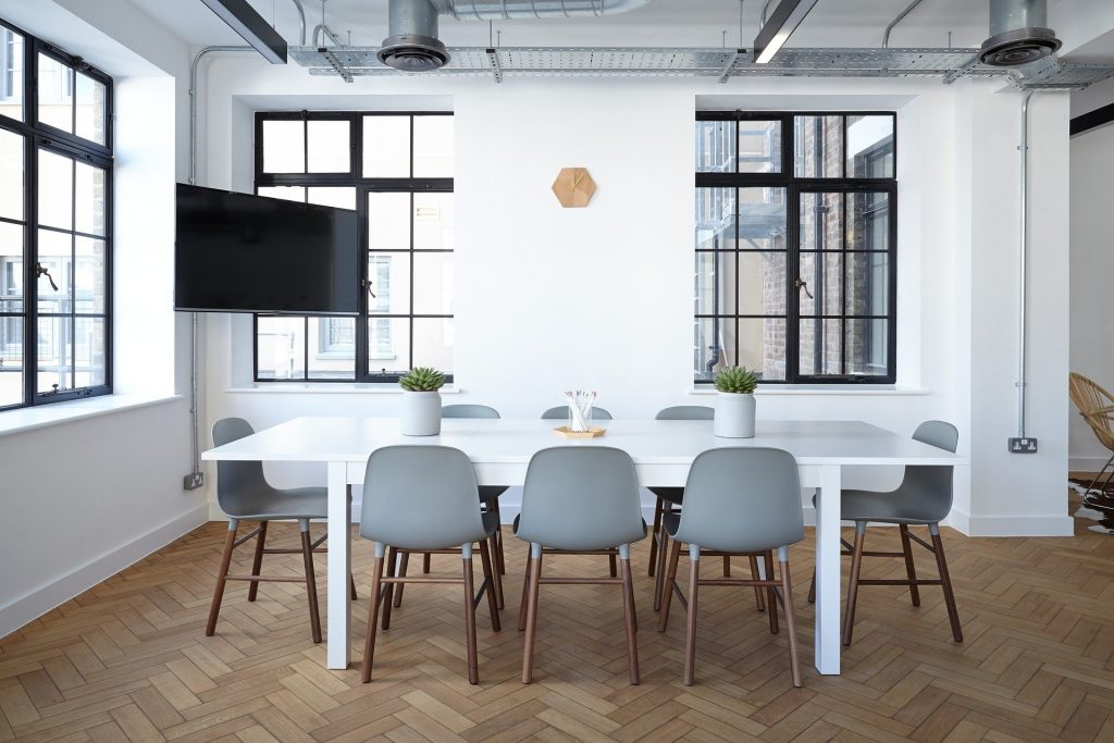 White Table with Grey Chairs In Corner Office